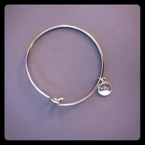 Silver plated bangle bracelet with charm.